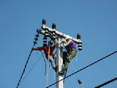 Two workers at work at the top of a distribution network pole