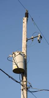 Photo of a transformer at the top of a distribution pole
